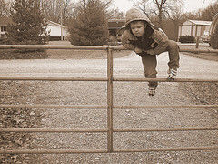 Kid jumping a gate